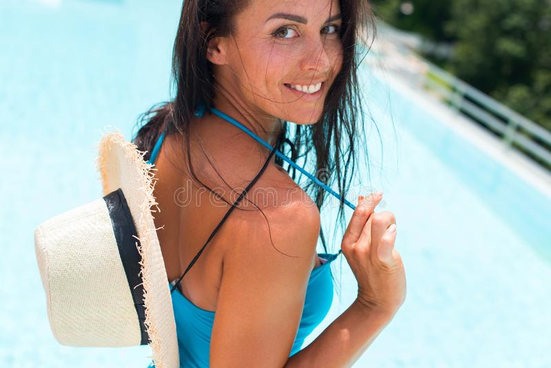 Happy brunette suntanned woman in blue swimsuit. And staw hat relaxing in swimming pool spa. Vacation and rest in tropical Thailand. Summer time. Ppoolside royalty free stock photo