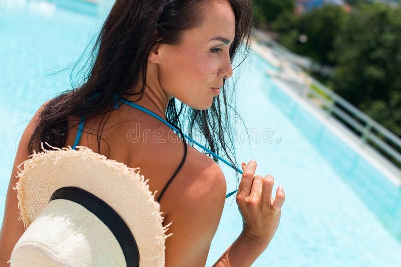 Happy brunette suntanned woman in blue swimsuit. And staw hat relaxing in swimming pool spa. Vacation and rest in tropical Thailand. Summer time. Ppoolside stock images