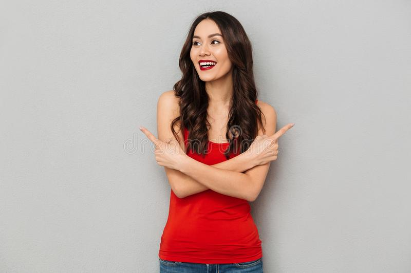 Happy brunette woman in casual clothes with crossed arms. Pointing to the sides while looking away over grey background stock image