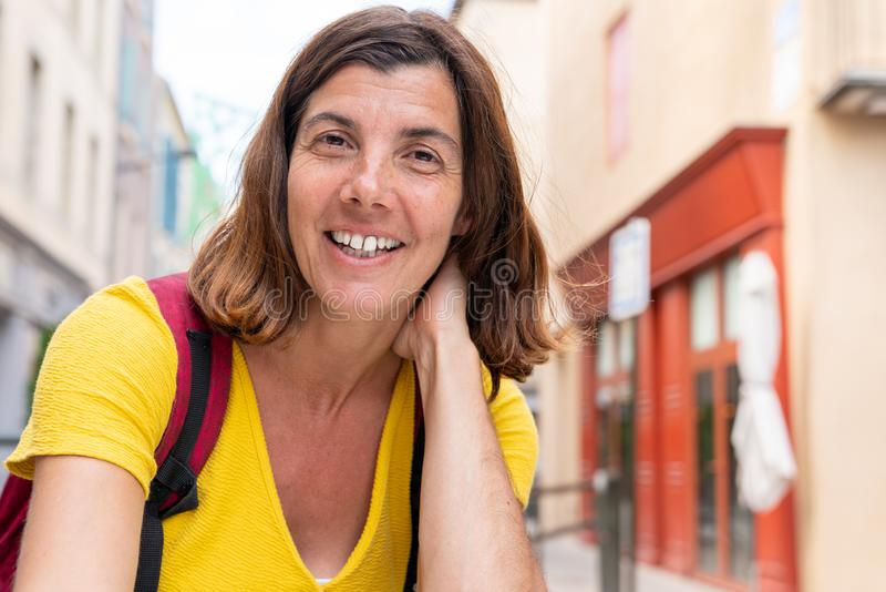 Happy brunette woman smiling happy tourist girl sitting in street summer cafe stock photo