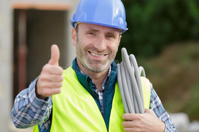 Happy builder man laughing and making thumbs up outdoors royalty free stock photography