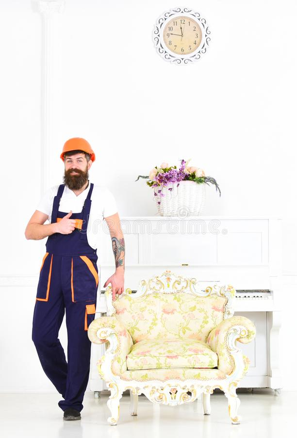 Happy builder relocating vintage armchair before redecoration. Smiling mover with thumb up isolated on white background royalty free stock photo