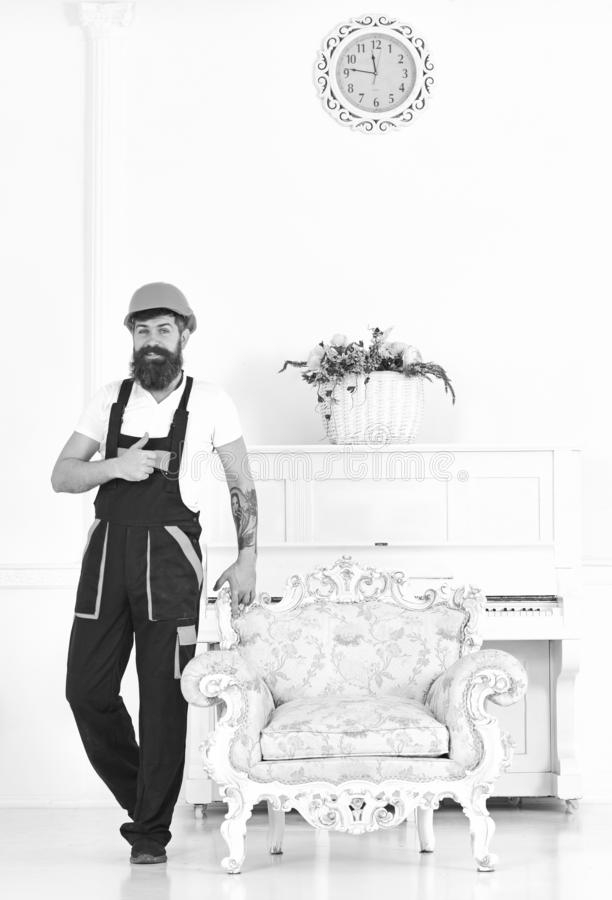 Happy builder relocating vintage armchair before redecoration. Smiling mover with thumb up isolated on white background stock photo