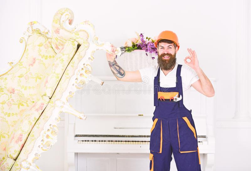 Happy builder relocating vintage sofa before redecoration. Smiling mover with stylish beard and mustache showing ok royalty free stock image
