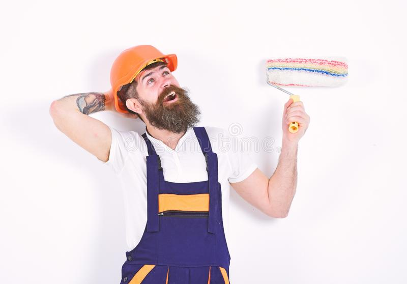 Happy builder singing in room. Man in orange helmet relaxing in front of white wall. Home redecoration and repairment royalty free stock photo