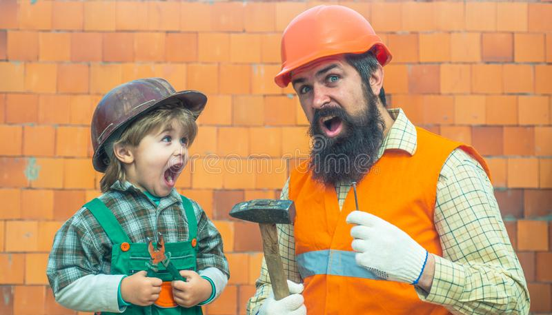 Happy builders. Father and son are screaming at a construction site. New house. The American dream. Happy family in a royalty free stock image