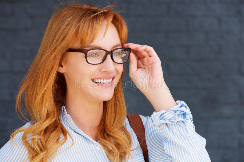 Happy business casual woman with hand to glasses. Close up portrait of happy business casual woman with hand to glasses royalty free stock image