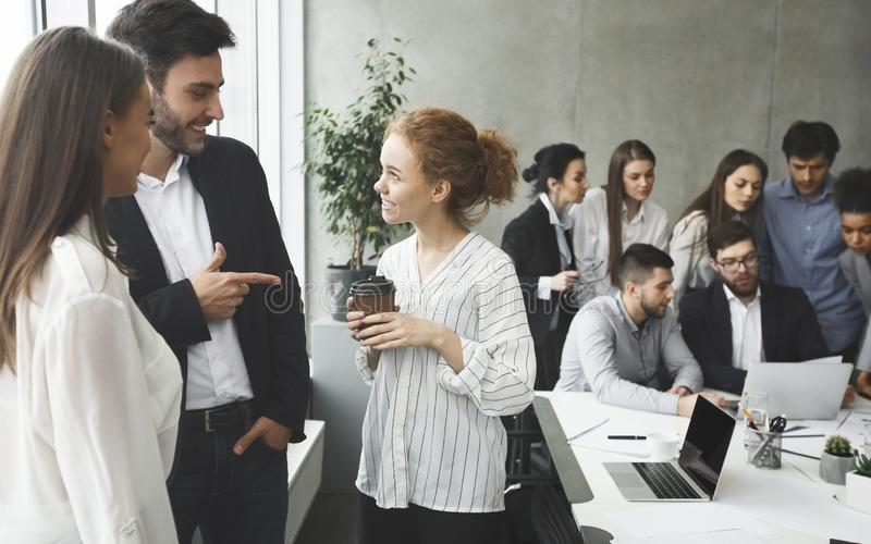 Happy business colleagues communicating in office during break stock image