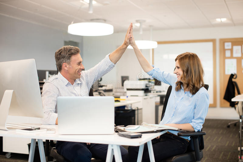 Happy business colleagues giving high five to each other stock images