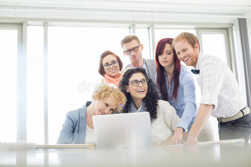 Happy business colleagues with laptop discussing in creative office stock images