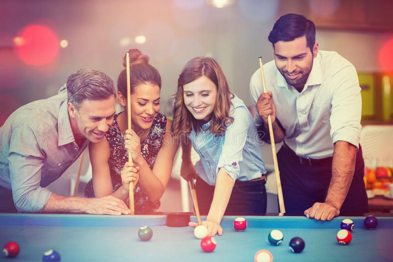 Happy business colleagues playing pool stock photography