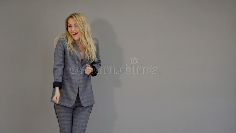 Happy business dancer girl in suit marking a successful deal and dancing freestyle in office on the grey background. royalty free stock images