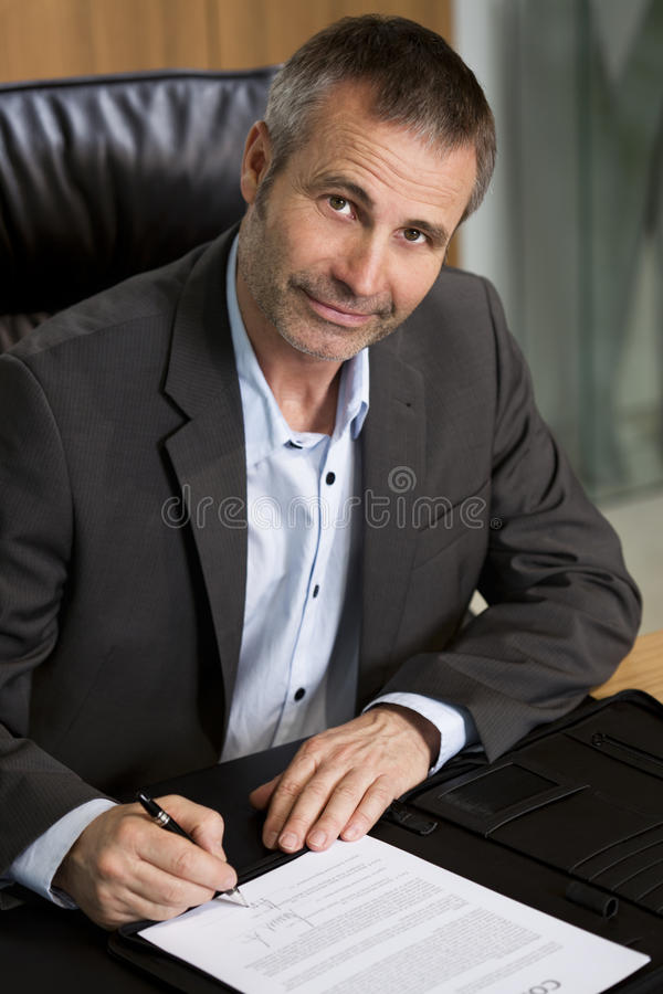 Happy business executive signing a contract. royalty free stock photography