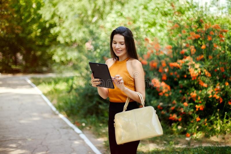 Happy business girl looking into the tablet, working anywhere royalty free stock photography