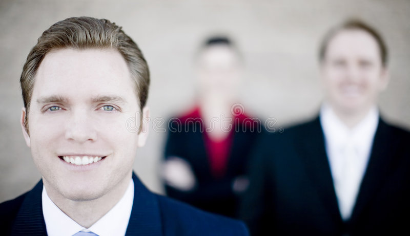 Happy business group. Close view of handsome businessman with businesspeople standing in background all looking at camera stock photo