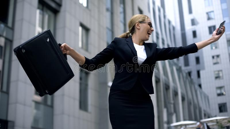 Happy business lady dancing joyfully after reading email about promotion, work royalty free stock images