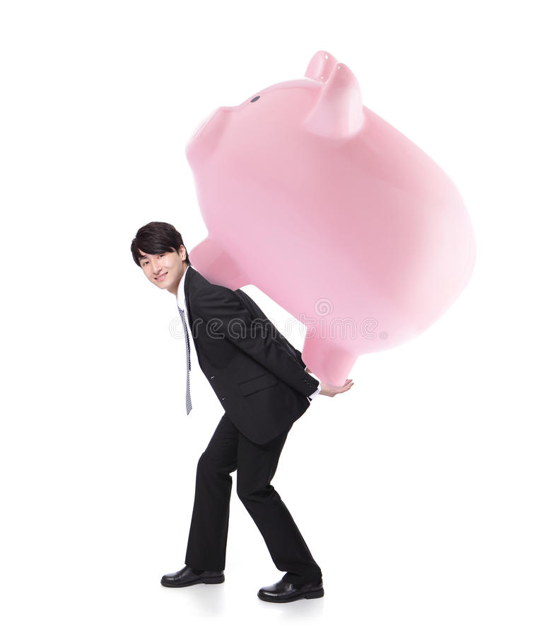 Happy business man carrying pink piggy bank stock image