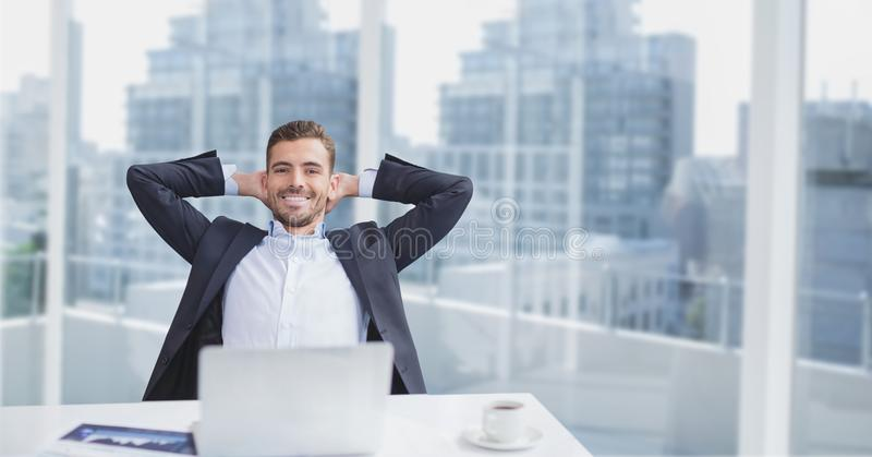 Happy business man at a desk sitting against city background. Digital composite of Happy business man at a desk sitting against city background stock photography