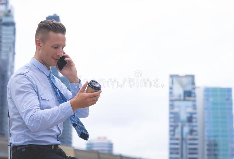 Happy Business man making call on his mobile phone and drink coffee royalty free stock images