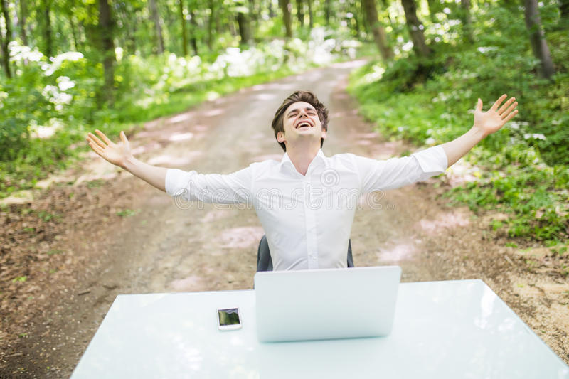 Happy business man with raised hands up celebrate great job or good news in front of laptop at office desk in green park. Business. Happy business man with royalty free stock image