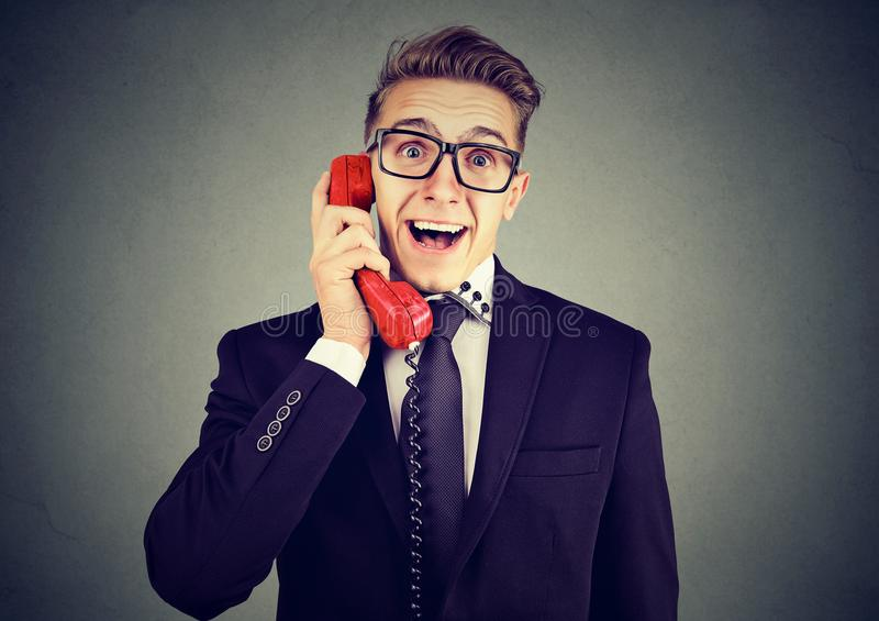 Happy business man receiving good news winning on the phone stock images