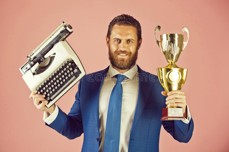 Happy business man with typewriter and golden champion cup. Business man with typewriter and golden champion cup, trophy, happy businessman or smiling lawyer stock image