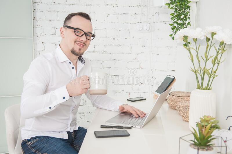 Happy Business man using laptop at home with cup of coffee. Freelance or distance study concept stock photography