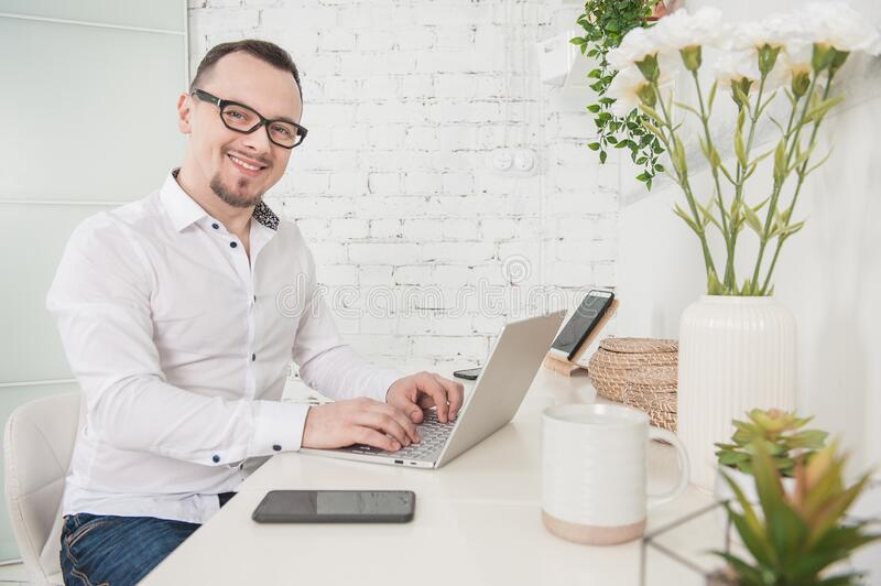 Happy Business man using laptop at home smiling. Freelance or distance study concept stock images