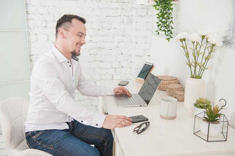 Happy Business man using laptop at home smiling. Freelance or distance study concept royalty free stock photo
