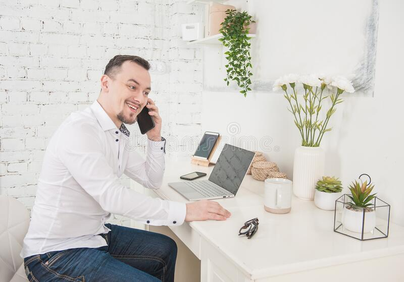 Happy Business man using laptop and smartphone at home. Freelance or distance study concept stock photo