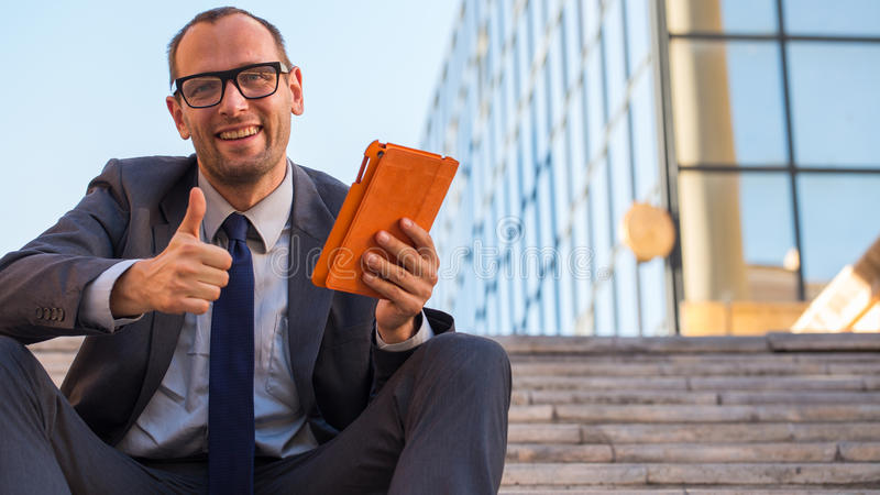 Happy business man using tablet PC in orange cover on a city street. Happy business man using tablet PC in orange cover on a city street royalty free stock images