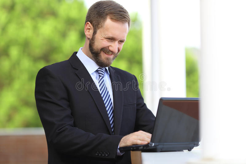 Happy business man working browsing internet in a laptop outdoor royalty free stock photo