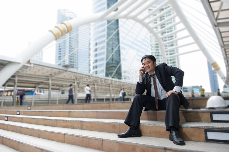 Happy business man is working by smart phone stock images