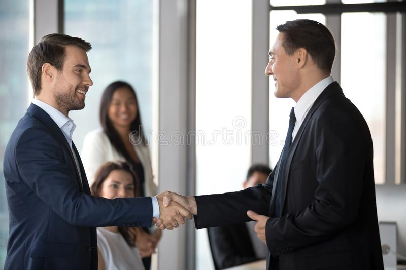 Happy business partners handshake congratulating with deal closing. Happy businessmen handshake greeting get acquainted at formal meeting in office, smiling male stock image