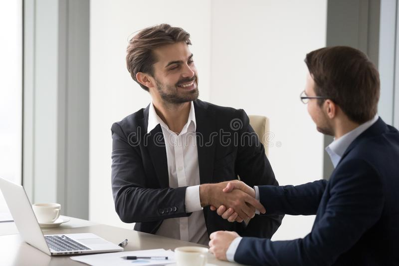 Happy business partners handshaking after successful meeting. Happy business partners shaking hands after successful negotiations in office, company CEO royalty free stock photos