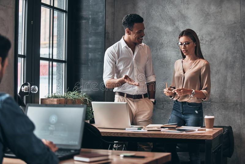 Happy business partners. Two young colleagues in smart casual we. Ar discussing something while spending time in the office royalty free stock photos