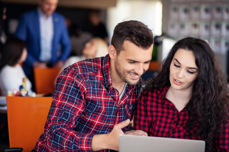 Happy business partners working on laptop. Teamwork, co-working concepts. royalty free stock photo