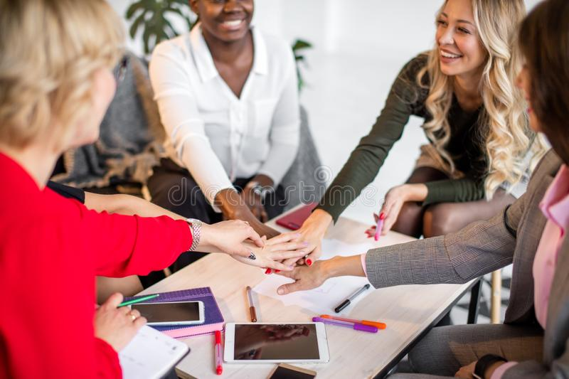 Happy business people agreement in office. Multiethnic group of african and caucasian gils giving high five at office, motivated by achievement or good work stock images