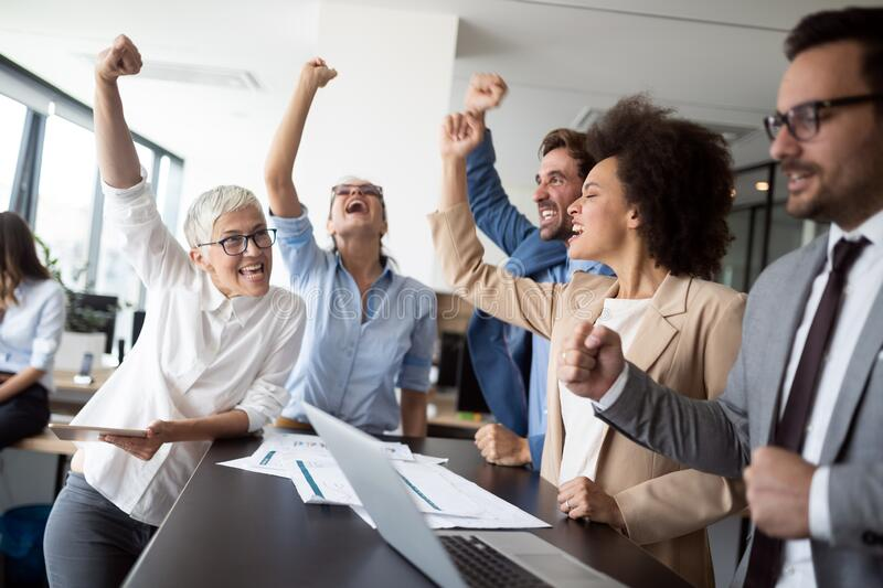 Happy business people celebrating success at company. royalty free stock image