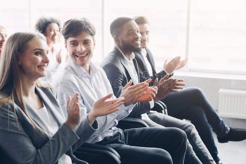Happy business people clapping hands during meeting conference stock images