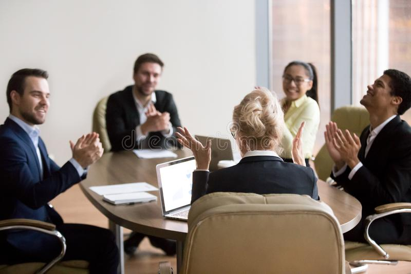 Happy business people congratulating partner woman in office at. Happy excited multiracial business team applauding and congratulating partner colleague women stock photo