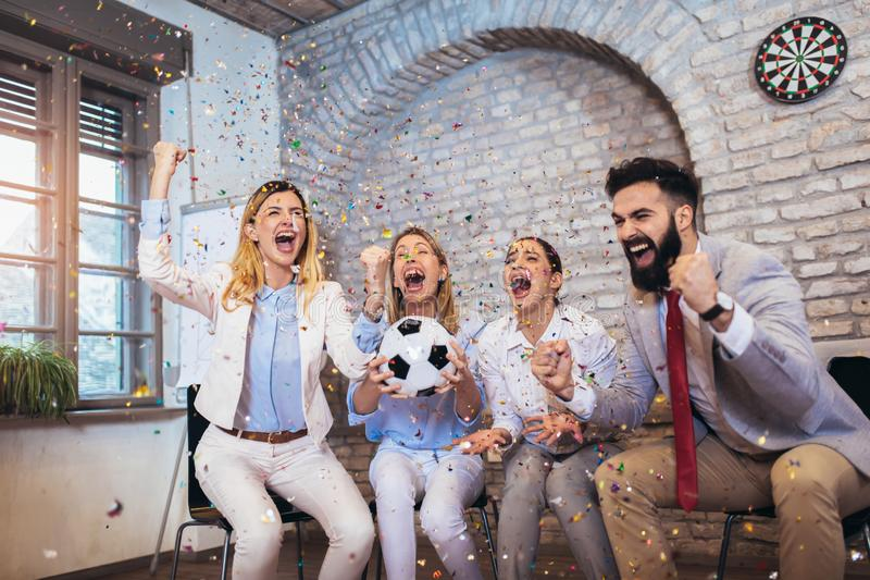 Business people or football fans watching soccer on tv and celebrating victory. Friendship, sports and entertainment concept. Happy business people or football stock image