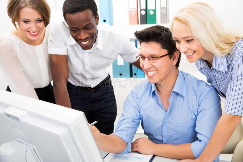Happy business people gathered around computer stock photography