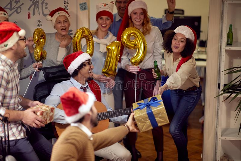 Happy business people have fun and dancing in Santa hat at Xmas party royalty free stock image