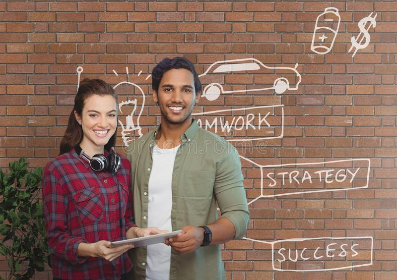 Happy business people holding a tablet against brick wall with graphics stock photo