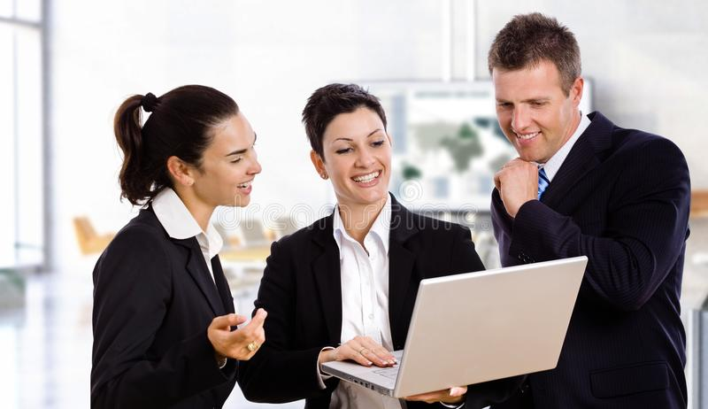 Happy business people with laptop stock image