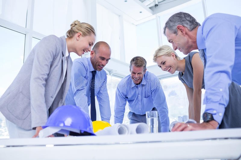Happy business people looking at construction plan royalty free stock images