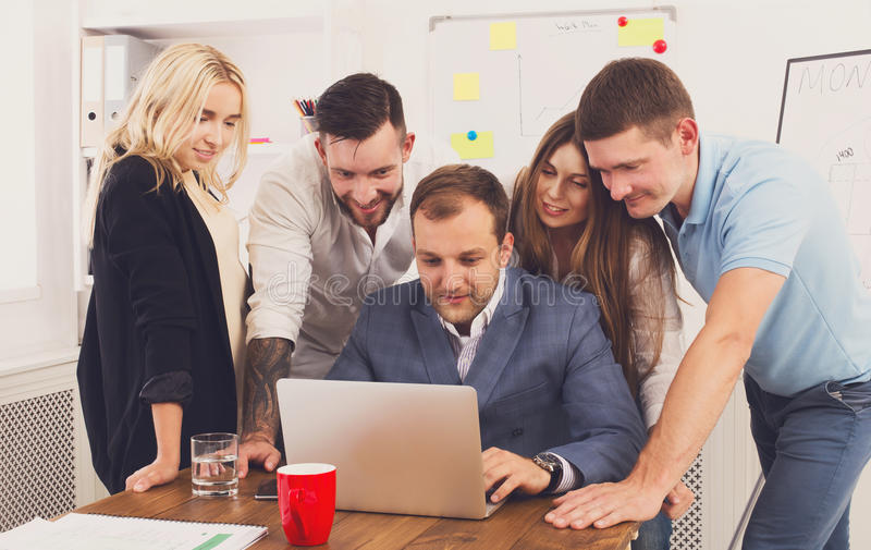 Happy business people team together look at laptop in office stock photography