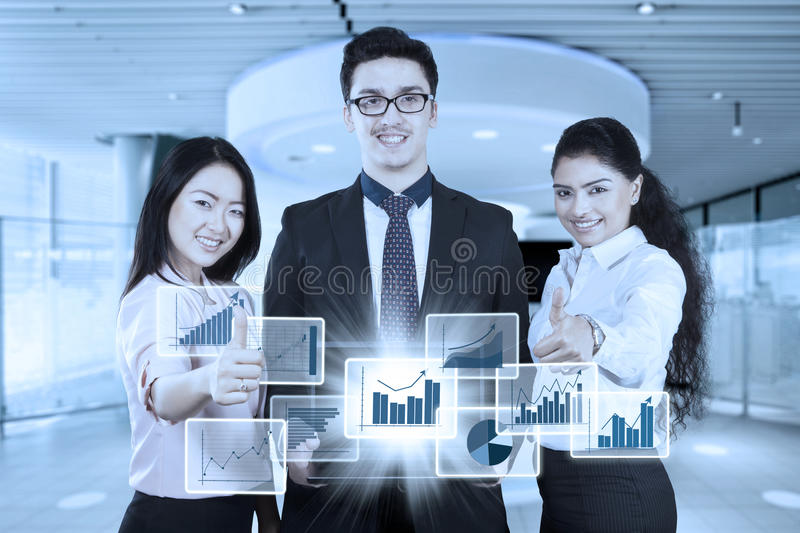 Happy business people with virtual business growth. Young business people showing virtual business growth on the laptop and thumbs up while smiling at the camera royalty free stock images