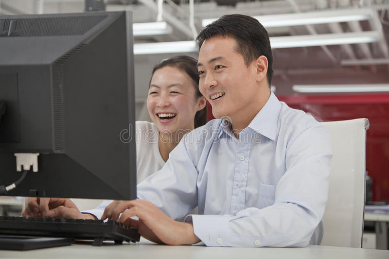 Happy business people working on their computer in the office stock photos